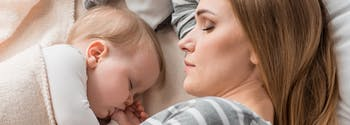 parent co-sleeping with baby in bed