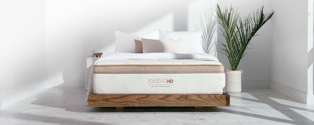 saatva heavy duty mattress inside bedroom with plant next to it