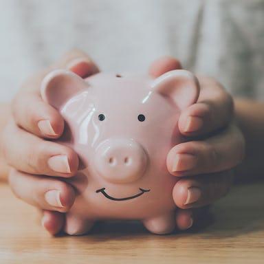 Man's hands holding a  piggy bank