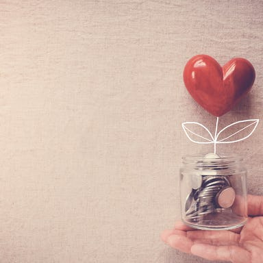 Hand holding a jar of heart tree growing on money coins