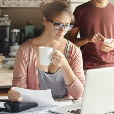 Young female having concentrated expression looking at screen of open laptop, holding paper and cup of coffee in her hands