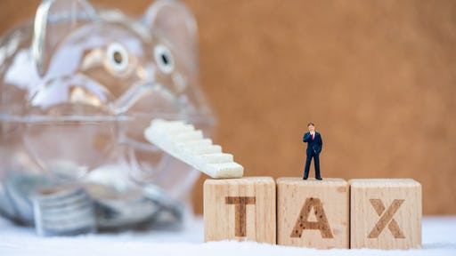 Miniature letter blocks that spell TAX with an escalator that steps up to a piggy bank that is saving money