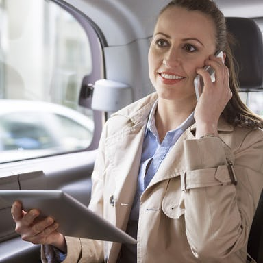 Woman making a phone call and using her tablet while seating the back seat of a car