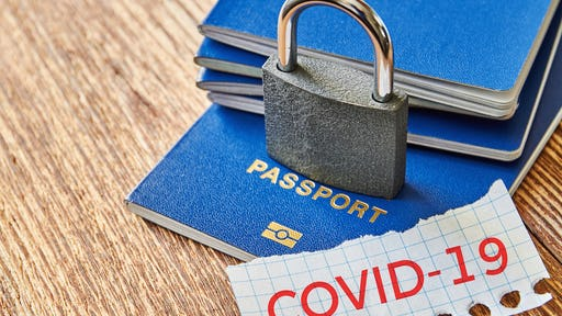 Stack of passports with a lock over them and a piece of paper with COVID-19 message