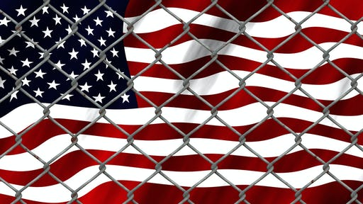 United States flag behind a fence