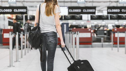 Girl carrying a trolley in the airport