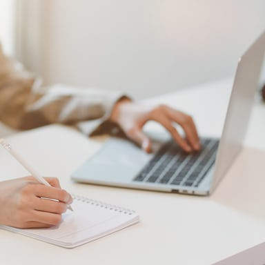 Businesswoman typing on laptop and writing on notebook
