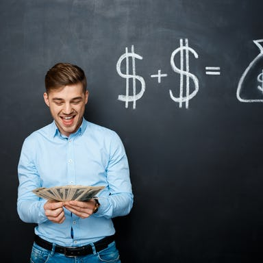Man holding several bills of U.S. dollars standing over a blackboard with drawn dollar signs