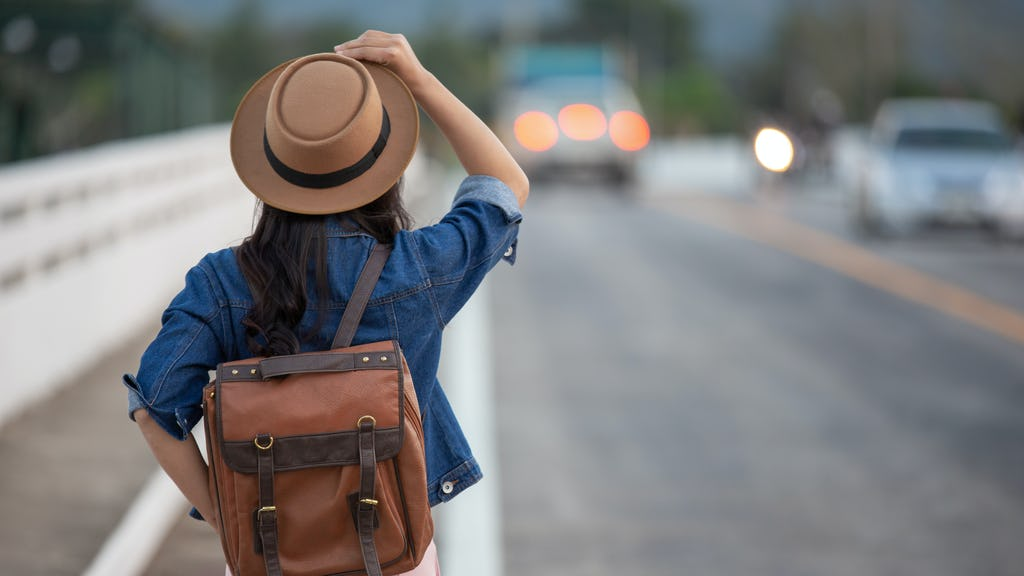 Girl traveling with a backpack in a road