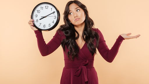Puzzled brunette woman with curly long hair holding clock showing time after 8 gesturing like she is late but not worried, over peach background
