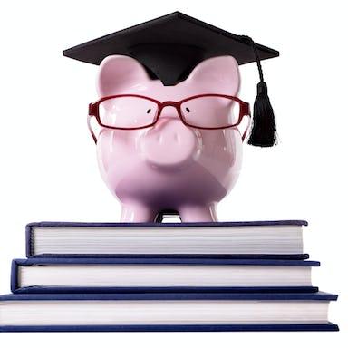 Piggybank wearing a graduate hat standing on top of three big books <a href=