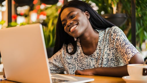 Young african woman siting at cafe smiling and working on laptop <a href=