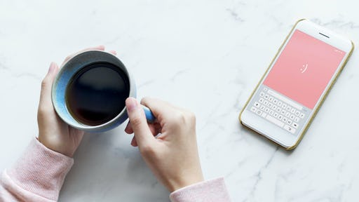 Hands holding a teacup with coffee and a mobile phone with a smile in the wallpaper