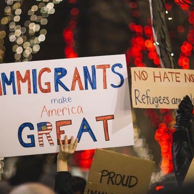 People protesting with banners and slogans supporting immigration
