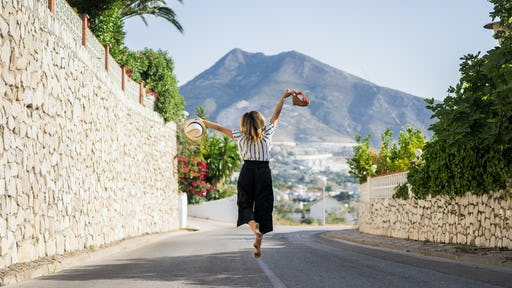 Girl happily jumping in the middle of the street