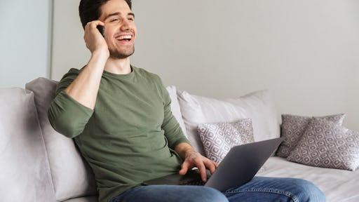 Smiling young man talking on mobile phone