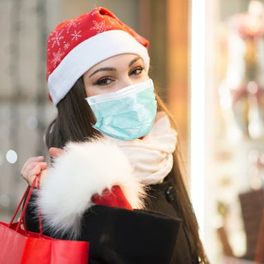 Woman wearing a red holiday hat and a mask with holiday lights on the background