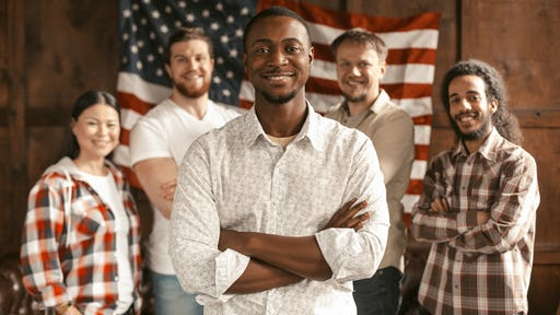 Diverse group of Americans standing  in front of an American flag