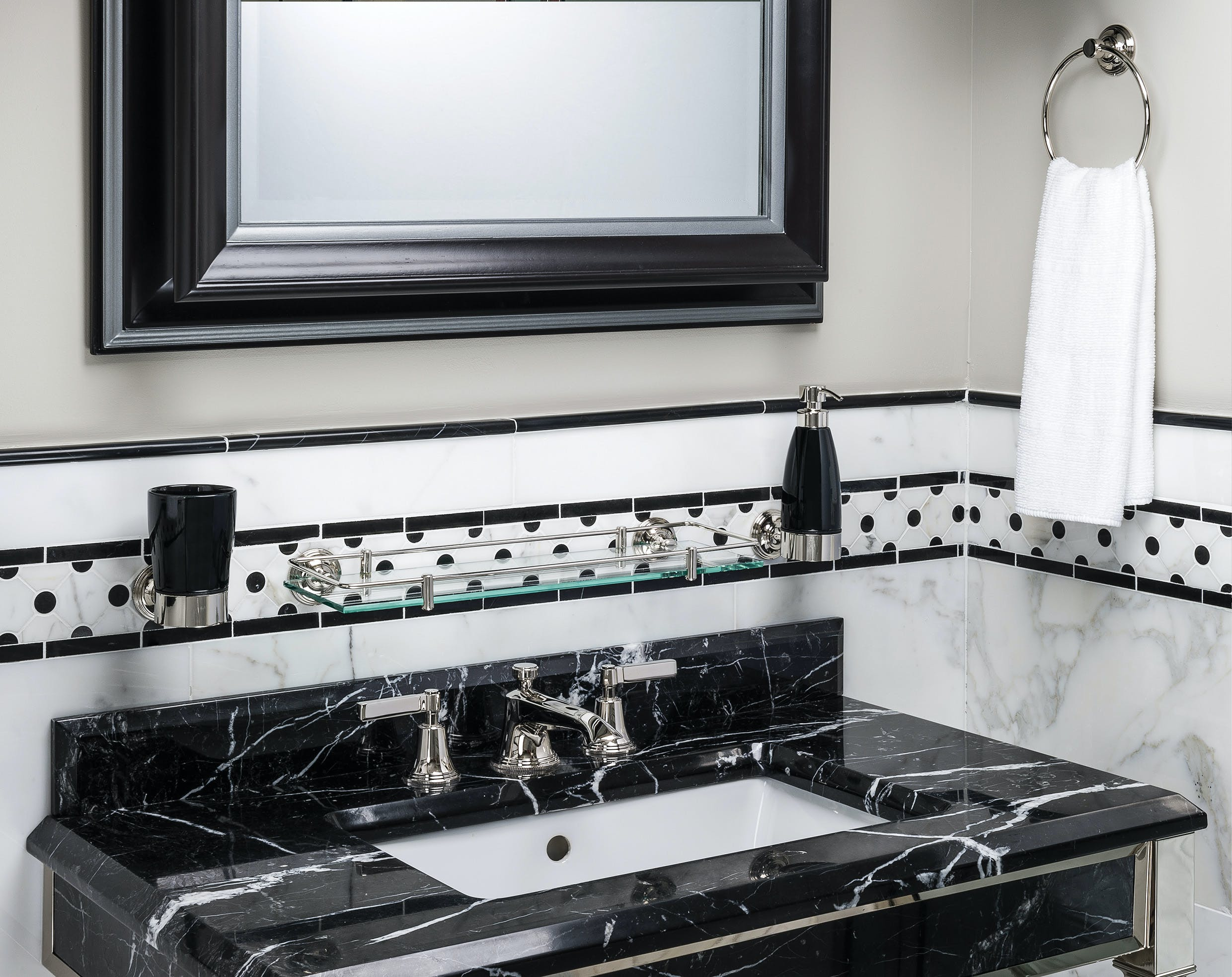 Luxury Art Deco taps mounted on a black marble basin
