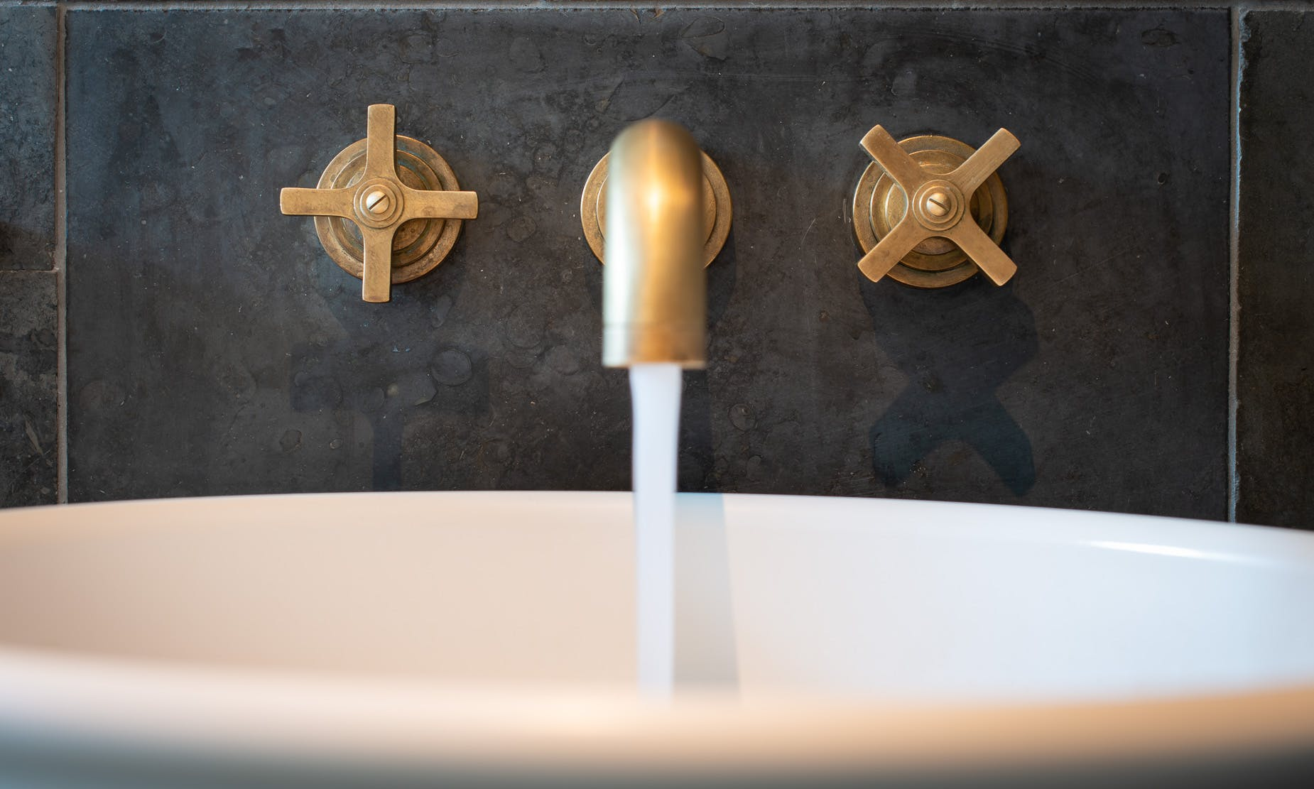 Samuel Heath Bauhaus inspired LMK Pure wall mounted tap in a natural urban brass finish showing patina.