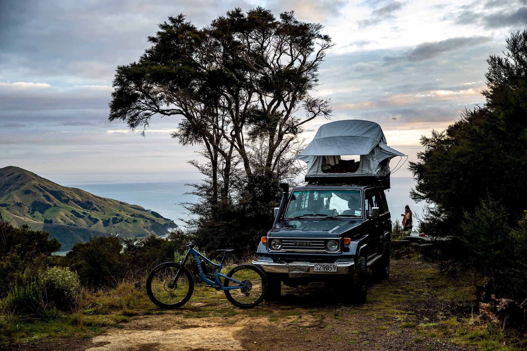 Anka Martin's 2022 Roubion next to her land cruiser with an open rooftop tent