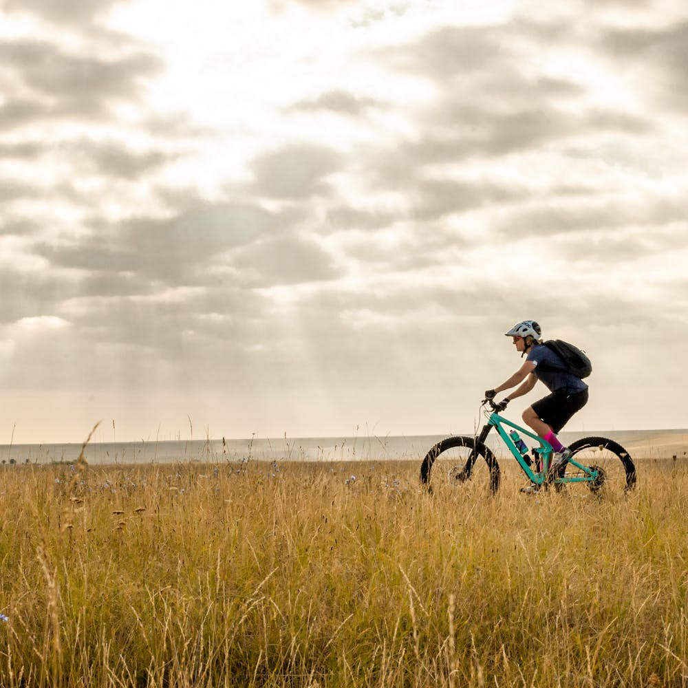 Mountain Biker riding a Santa Cruz Bicycle through a field in Colorado