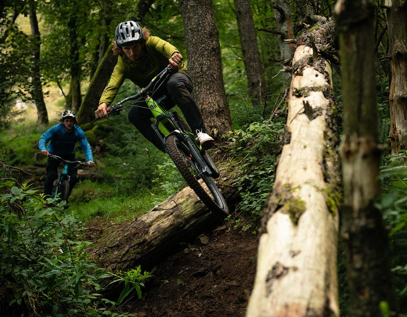 Two mountain bikers in woods on 27.5 Nomads