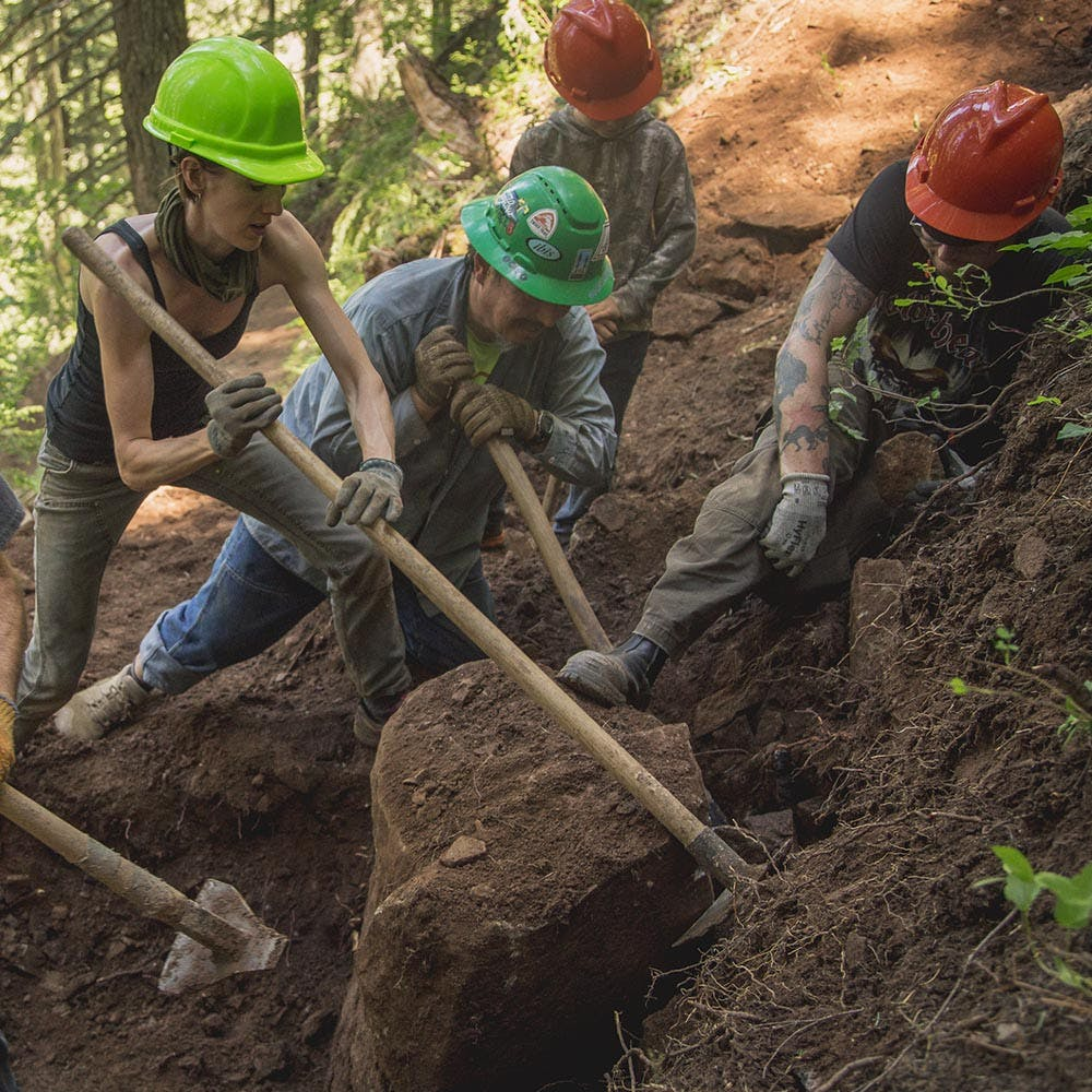 Trail workers removing a tree stump in Oregon