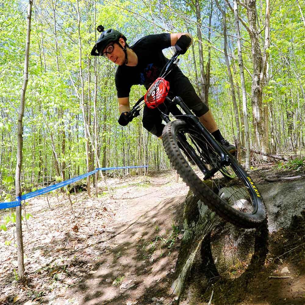 A mountain biker riding off of a rock ledge