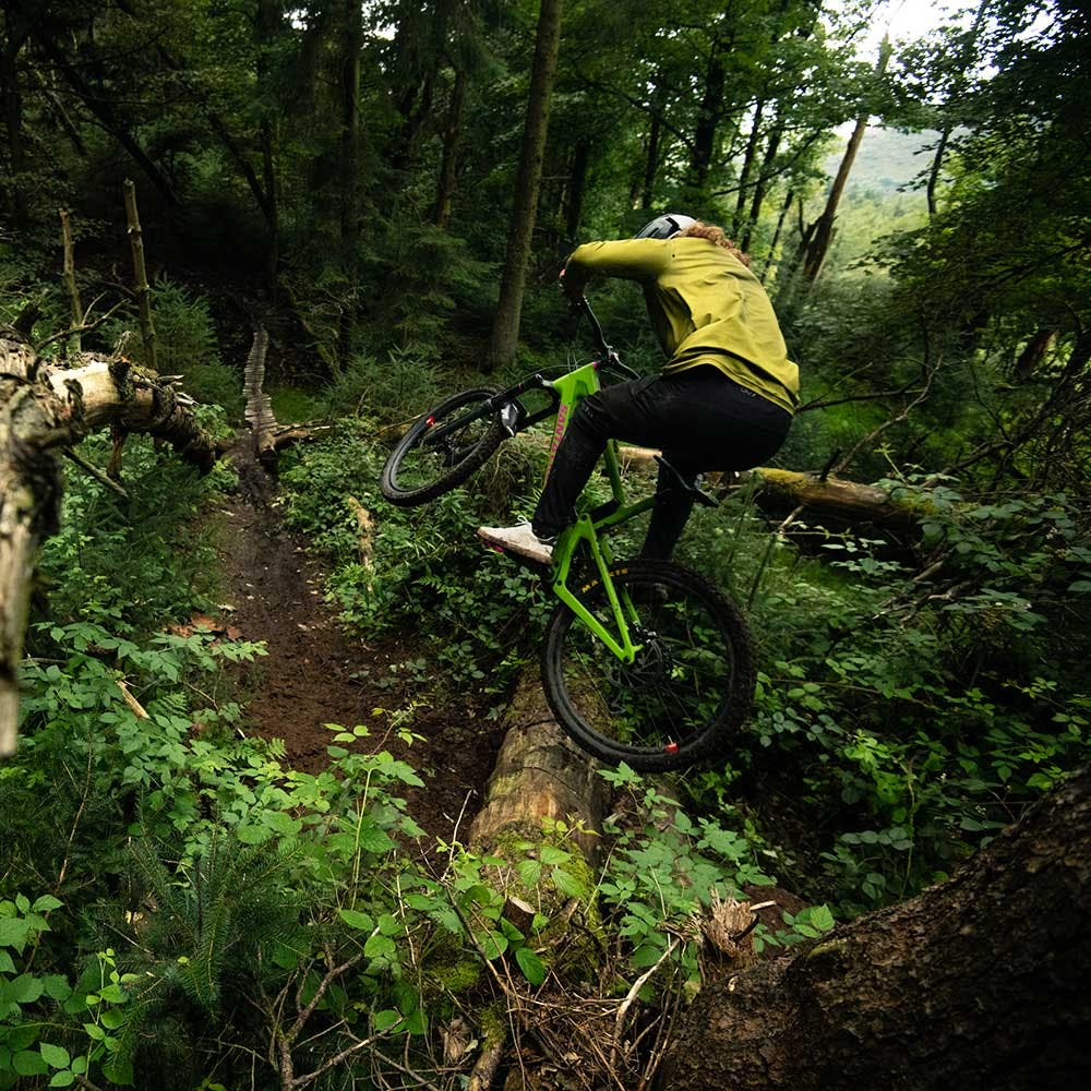 Mountain biker jumping Nomad onto trail