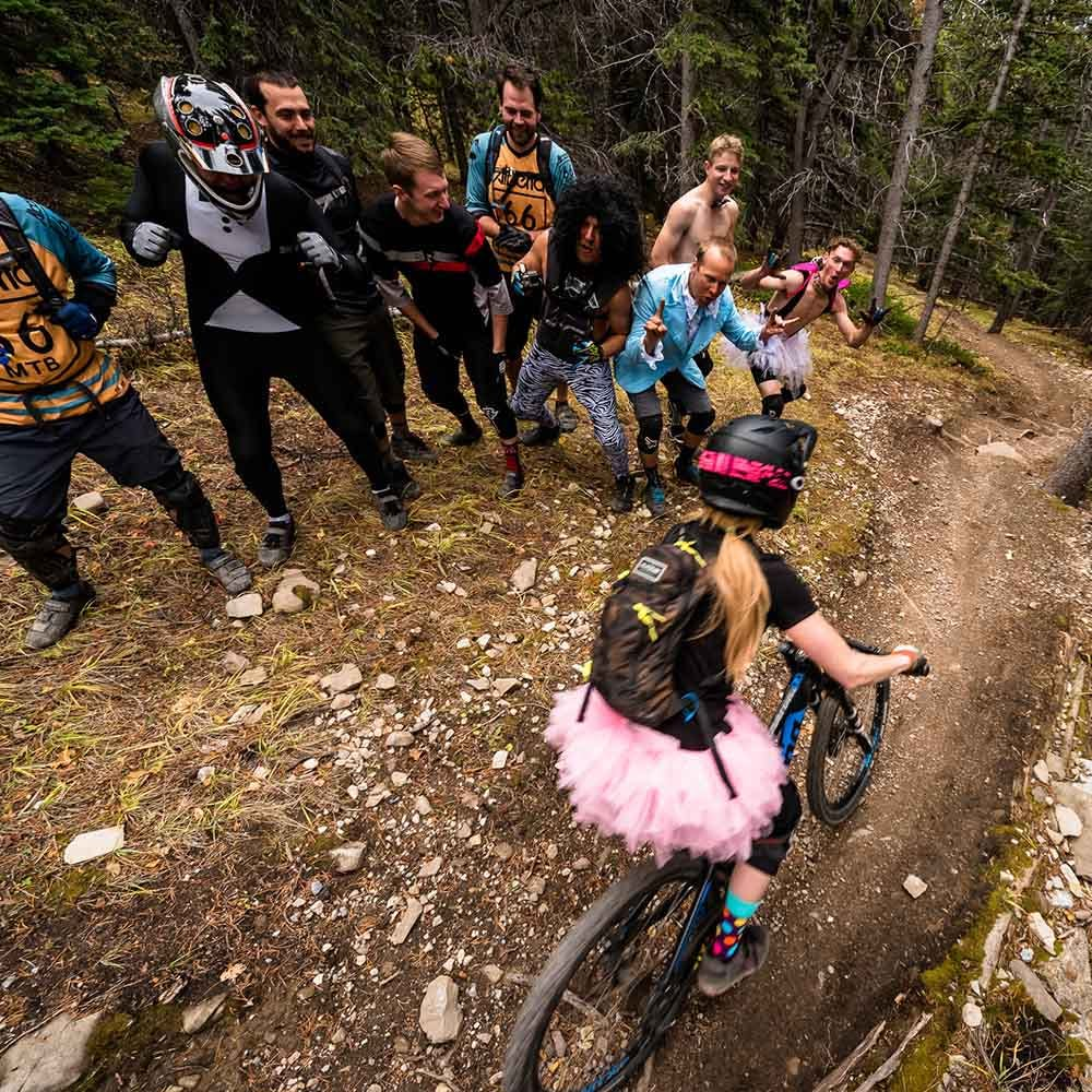Hecklers cheering on a mountain biker wearing a pink dress