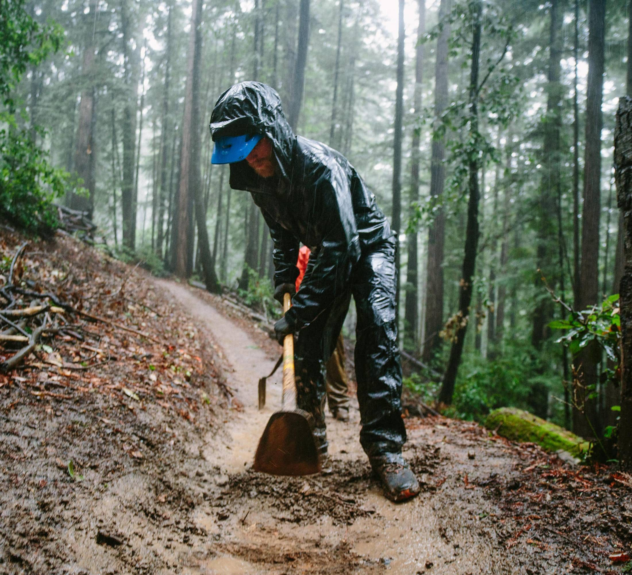 Trail maintenance with Land Trust of Santa Cruz County in California - Trail worker digging up a portion of the trail