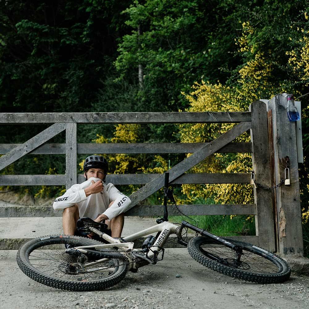 Mountain biker sitting next to Tallboy