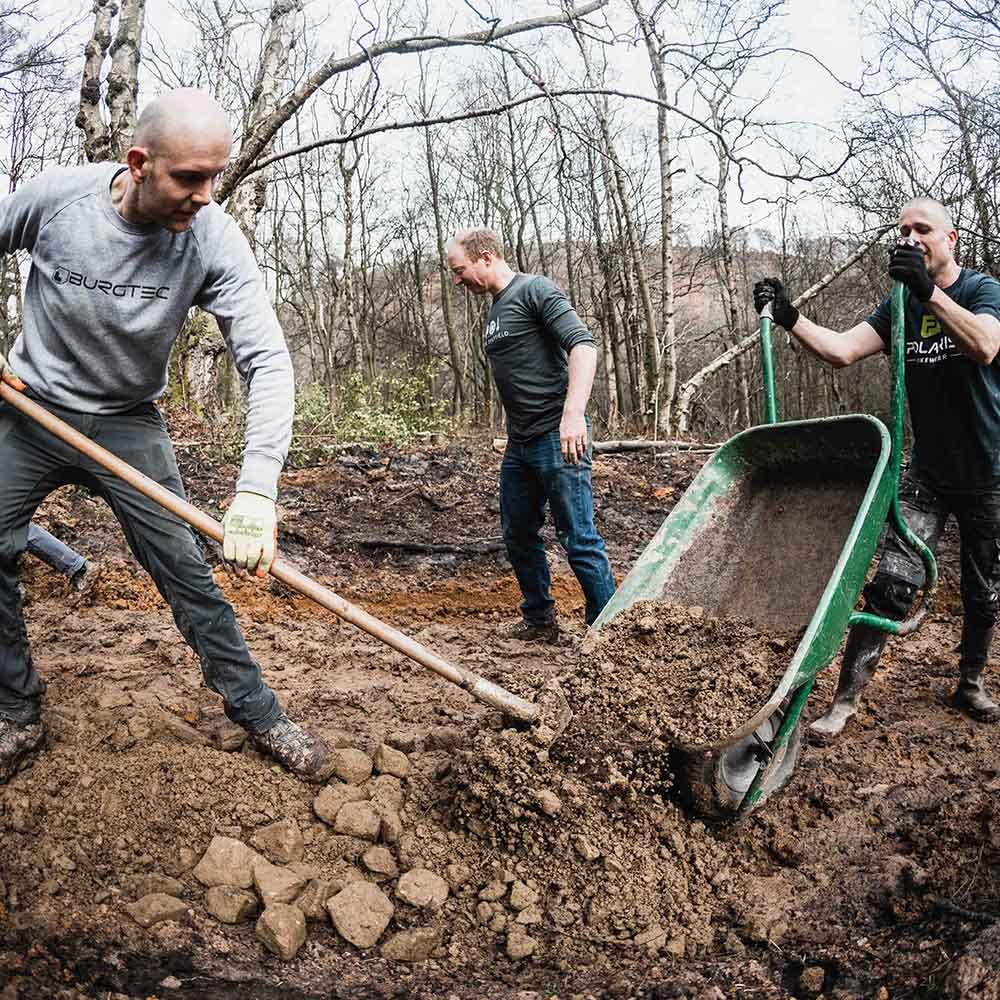 Trail builders moving dirt out of a wheelbarrow