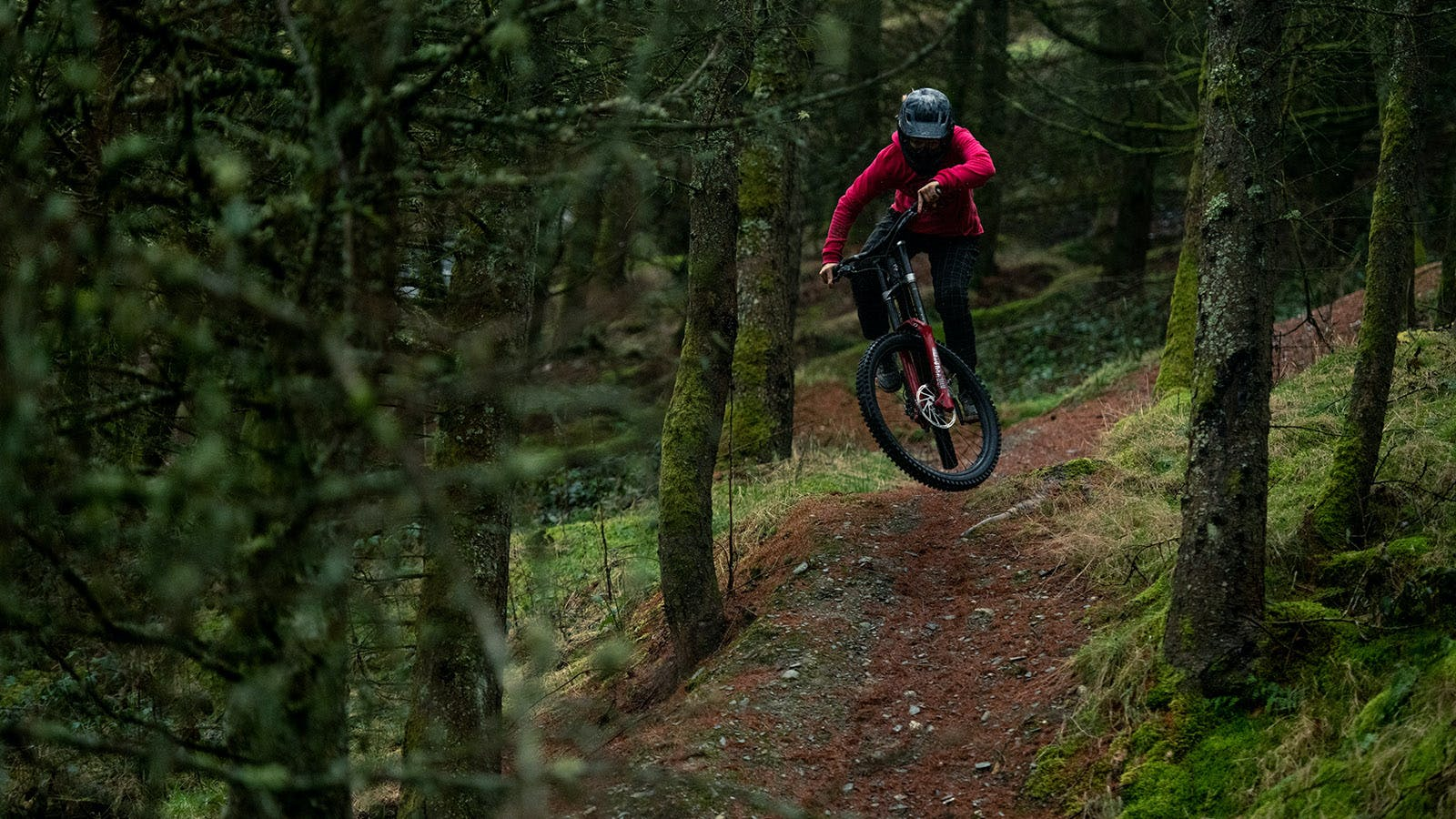 Veronique Sandler riding her downhill bike in the woods