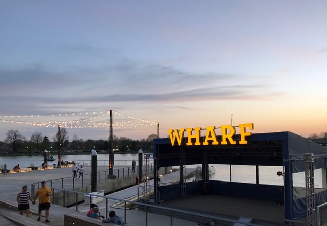 Dusk sunset overlooks a large neon sign that reads Wharf.