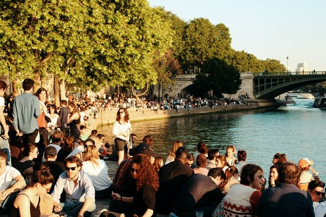 Hundreds of people gather and sit around a sunny riverway during a summers day in Paris, France.