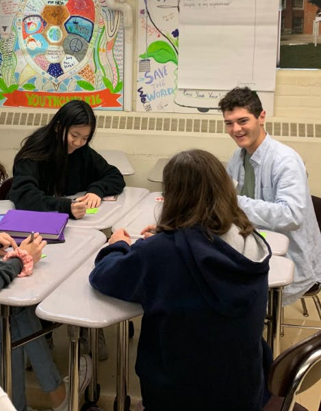 A Scout Labs team member sitting at a group of desks, engaged in conversation with a young student