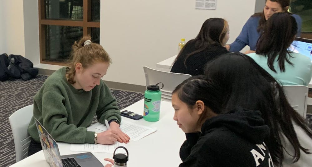 Women sitting at a table taking notes, facing two students as they look at a laptop screen