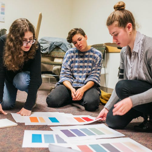 Three students work on selecting colors for a Scout project.