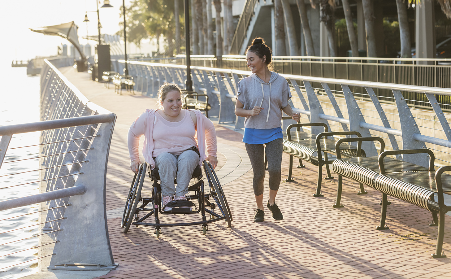 Two ladies smiling whilst moving outside, lady on the left is in a wheelchair and lady on the right is running whilst smiling at her.