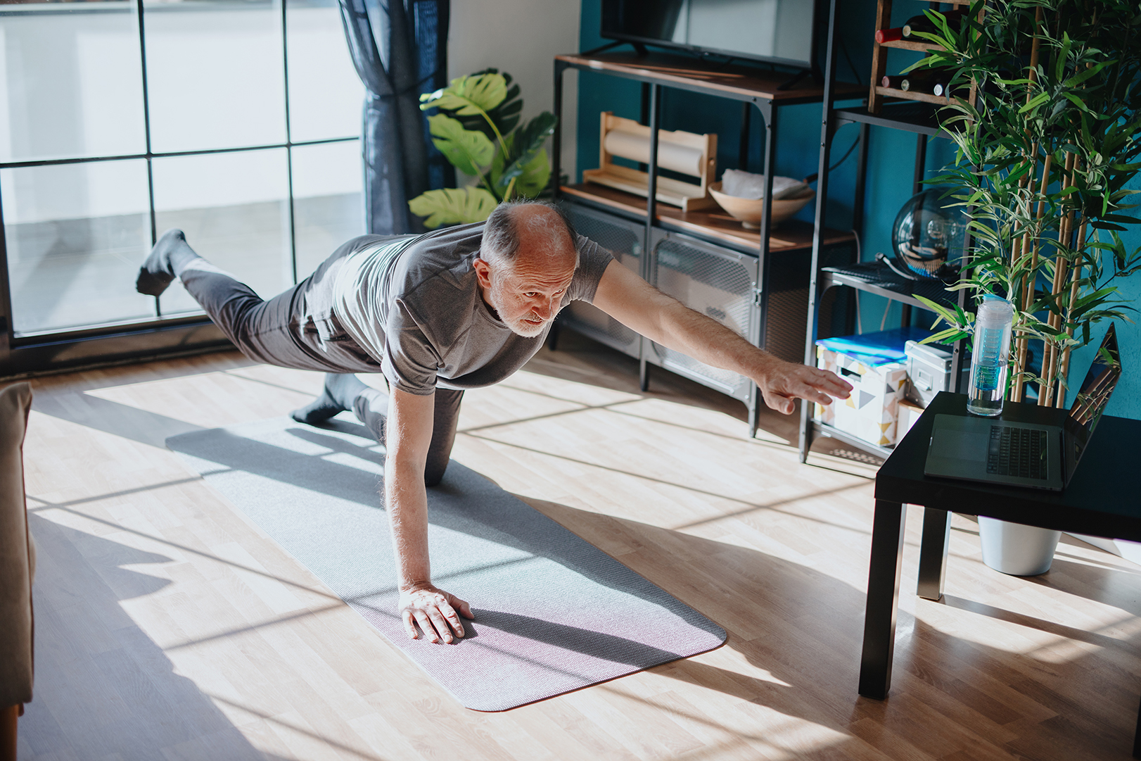 Man exercising on a yoga mat in his home. One arm is outstretched towards his laptop with his leg outstretched towards the window.