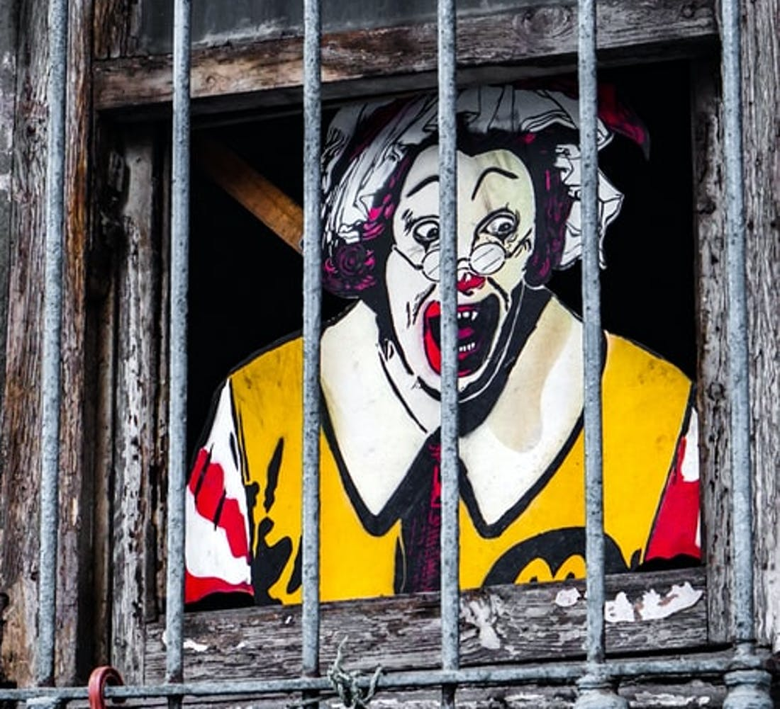 Ronald McDonald screaming behind bars in a wooden frame
