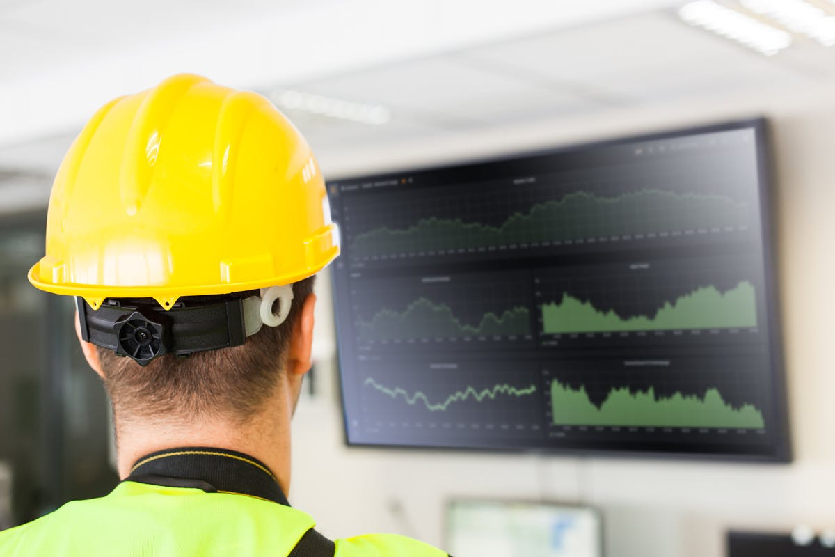 Man wearing a yellow hardhat and high-vis jacket looks at a screen showing data
