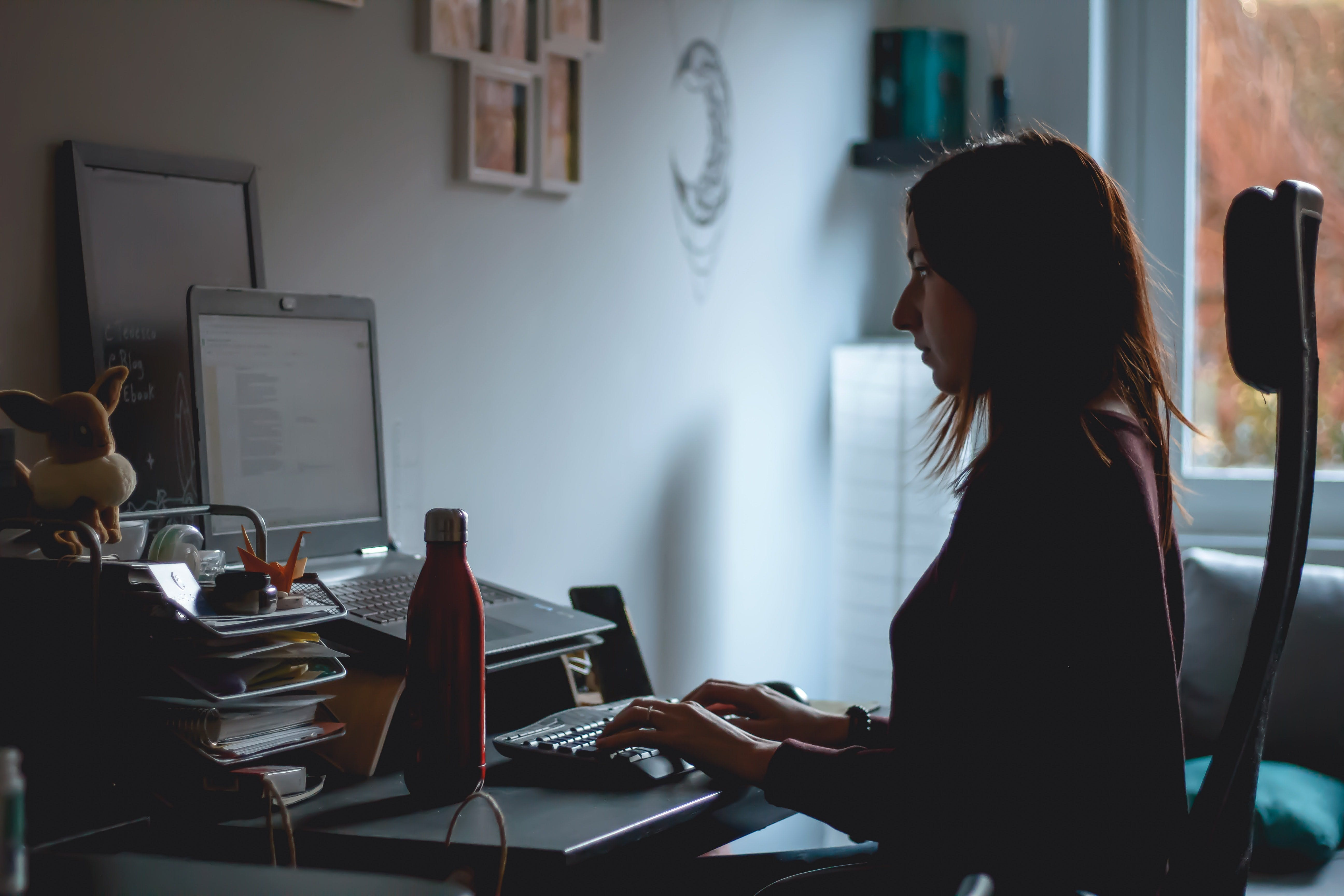 susanna marsiglia unsplash photo woman sat at desk working from home posture sitting back ache nhs advice repetitive strain injury avoid office chair work teaching learning scr tracker single central register record tracking vetting checks