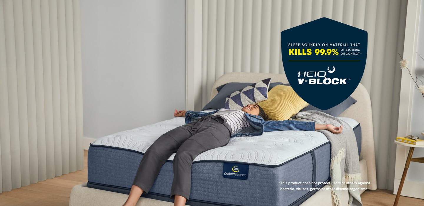 A woman lays on a Serta Perfect Sleeper mattress in a bedroom. A blue shield is overlaid on the image with text that reads: Sleep soundly on material that kills 99.9% of bacteria on contact. HeiQ V-Block. This product does not protect users or others against bacteria, viruses, germs or other disease organisms.