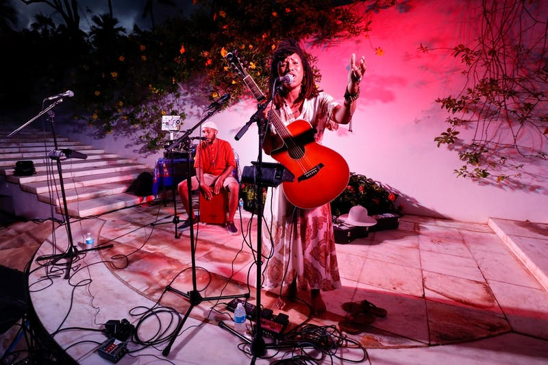 Close-up of Aja Black of the Reminders, holding a guitar, with Big Samir in the background on the Lower Lawn marble staircase at Shangri La.