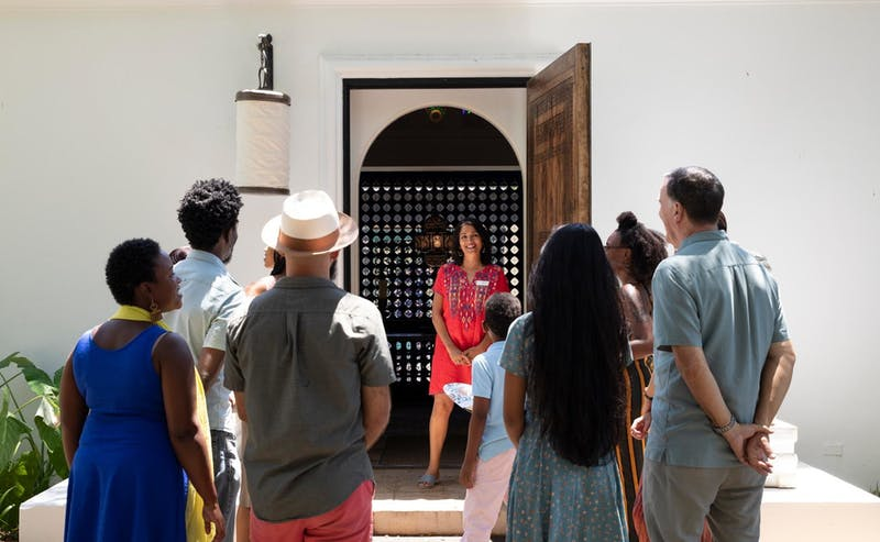 Woman (tour guide) in a red dress at the entrance to the museum with eight people surrounding.