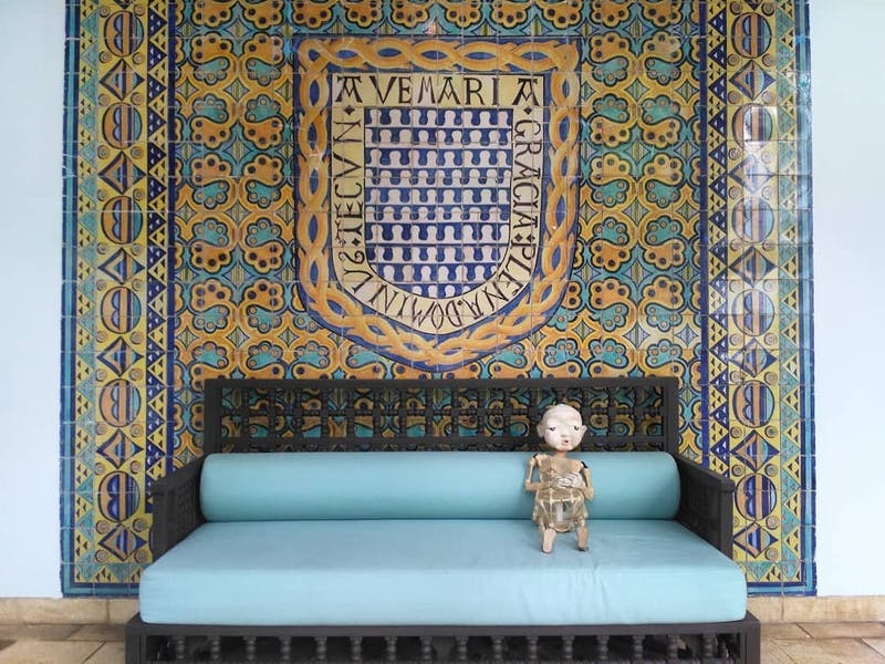 Papermoon Puppet vacantly staring into the distance while sitting on a teal couch in front of a blue, teal, and yellow tile panel.