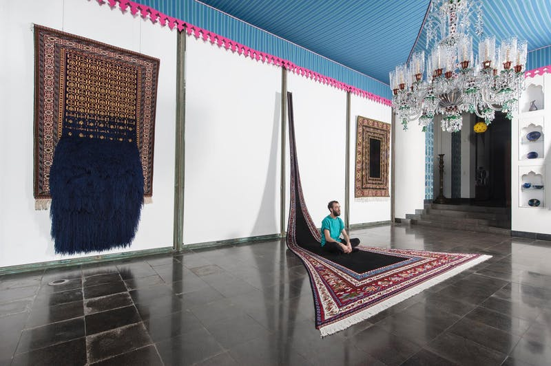 The Textile Gallery (formerly the Dining Room) at Shangri La with three of artist Faig Ahmed's works on display. Ahmed is sitting on one of his large-scale carpet works.
